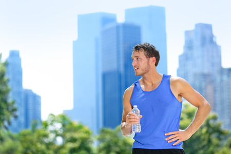 jogging: Sport man drinking water bottle in New York City. Male runner sweaty and thirsty after run in Central Park, NYC, Manhattan, with urban buildings skyline in the background.