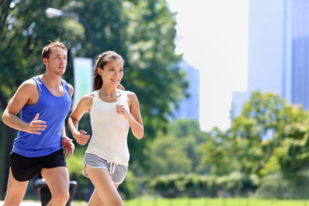cardio fitness: Runners jogging in New York City Central Park, USA. Healthy couple of new yorkers athletes running in summer sun working out a cardio exercise on Manhattan, United Sates of America.