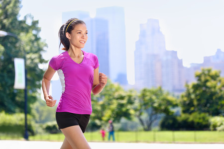 Run woman exercising in Central Park New York City with urban background of skyscrapers skyline. Active Asian female runner running with purple t-shirt and shorts sportswear. Stock Photo