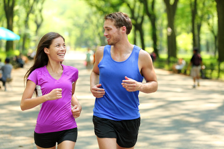 hombres haciendo ejercicio: Ejecuci�n de capacitaci�n pareja en Central Park, Nueva York (NYC). Los corredores felices hablando juntos durante la marcha en el camino comercial a pie famosa bajo los �rboles en Manhattan, fitness urbano. Foto de archivo
