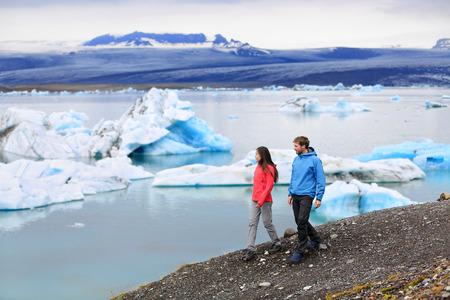 jokulsarlon: People hiking on Iceland Jokulsarlon glacial lagoon  glacier lake. Active lifestyle couple tourists walking enjoying beautiful Icelandic nature landscape with Vatnajokull in backround.
