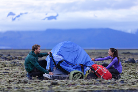 Tent - people pitching tent on Iceland at dusk. Couple setting up camp for night after hiking in the wild Icelandic nature landscape. Multicultural Asian woman and Caucasian man healthy lifestyle. Imagens