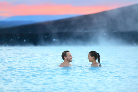 hot love: Hot spring geothermal spa on Iceland. Romantic couple in love relaxing in hot pool on Iceland. Young woman and man enjoying bathing relaxed in a blue water lagoon Icelandic tourist attraction. Sunset.