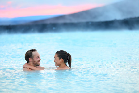hot water geothermal: Hot spring geothermal spa on Iceland. Romantic couple in love relaxing in hot pool on Iceland. Young woman and man enjoying bathing relaxed in a blue water lagoon Icelandic tourist attraction. Sunset.