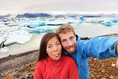 self   portrait: Funny selfie couple taking self portrait photograph on Iceland having fun on travel by Jokulsarlon glacial lagoon  glacier lake. Tourists enjoying beautiful Icelandic nature landscape Vatnajokull.