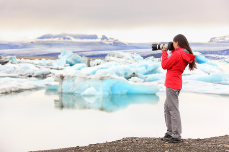 Nature landscape photographer taking picture photos with SLR camera on Iceland Jokulsarlon glacial lagoon / glacier lake. Woman taking photograph of beautiful Icelandic nature with Vatnajokull. Archivio Fotografico