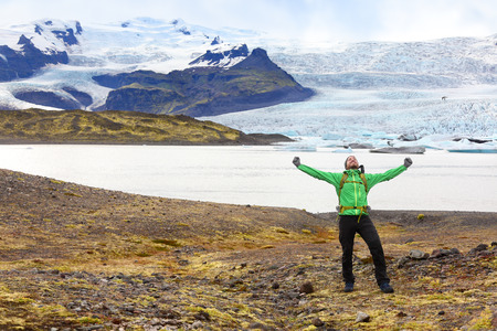 fjallsarlon: Hiking adventure travel man cheering happy on hike on Iceland. Hiker cheerful at glacier and glacial lagoon  lake of Fjallsarlon, Vatna glacier, Vatnajokull National Park. Icelandic nature landscape.