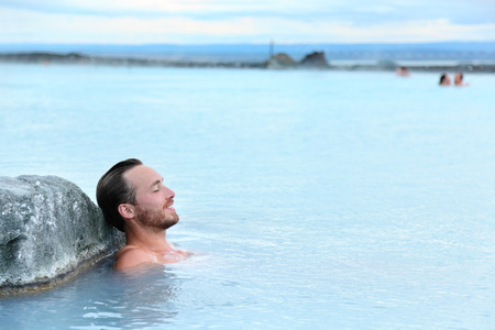 bathing man: Geothermal spa. Man relaxing in hot spring pool on Iceland. Young man enjoying bathing relaxed in a blue water lagoon Icelandic tourist attraction.