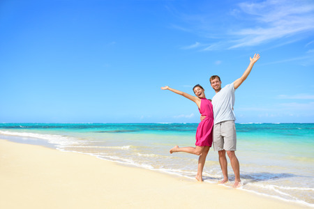 Freedom on beach vacation - happy carefree winning couple with arms up showing happiness and fun on paradise beach with perfect pristine turquoise water in sunny tropical getaway Banque d'images