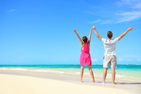 Happy free couple cheering on perfect beach travel holiday. Rear view of unrecognizable young people with arms raised to the sky praising the sun or showing success and freedom during summer vacation.