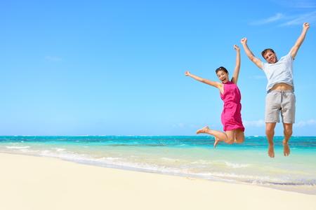 gente saltando: Turistas pareja feliz que salta en vacaciones en la playa. Concepto del recorrido de la joven pareja vítores para las vacaciones de verano que muestran el éxito, la felicidad y la alegría en perfecta playa tropical arena blanca bajo el sol.