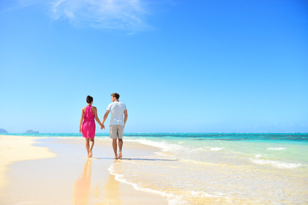in behind: Honeymoon couple holding hands walking on perfect white sand beach. Newlyweds happy in love relaxing on summer holidays in sunny tropical paradise destination. Travel vacation concept.