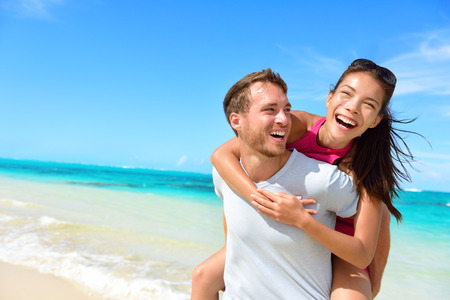 Happy couple in love on beach summer vacations. Joyful Asian girl piggybacking on young Caucasian boyfriend playing and having fun in sunny tropical destination for travel holiday.
