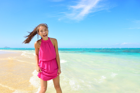 wet dress: Asian Chinese tourist woman having fun on beach. Young mixed race female adult playing in water wearing pink halter sundress laughing during summer travel holidays. Tropical sunny destination.