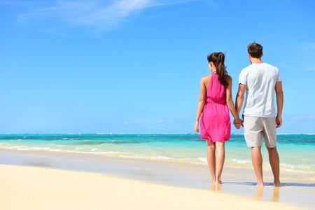 beachwear: Summer holidays - couple on tropical beach vacation standing in white sand relaxing looking at ocean view. Romantic young adults holding hands in beachwear with pink dress and surf shorts in love.