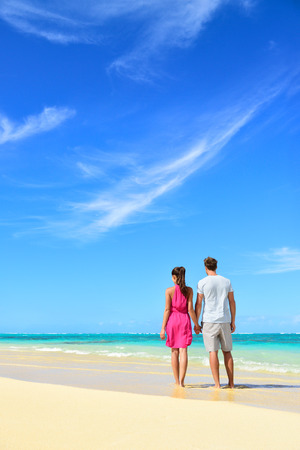 Beach vacation couple relaxing on summer holidays. Young people standing from behind holding hands looking at the ocean, vertical crop with a lot of copy-space in the blue sky. Travel concept. Stock Photo
