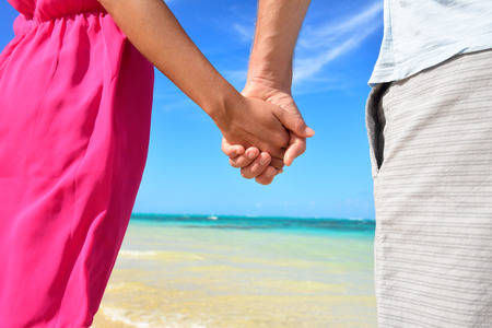 couple nature: Holding hands romantic newlyweds couple on beach. Closeup of male and female hands with a sunny blue beach background as honeymoon concept or happy relationship during travel summer holidays.
