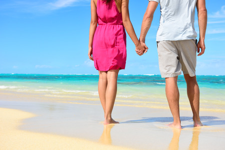 Beach couple in love holding hands on honeymoon. Lower body crop showing pink dress, casual beachwear, legs and feet of romantic newlyweds people standing on white sand on travel summer vacations.
