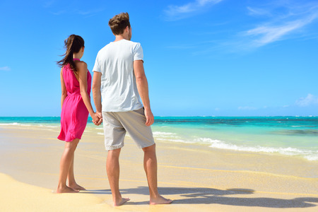 Beach couple looking at ocean view from behind. Unrecognizable couple standing on white sand in pink dress and casual shorts holding hands relaxing on summer travel vacations in tropical destination.