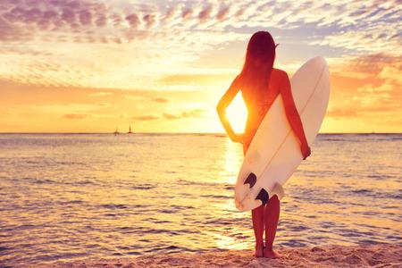 Surfer girl surf regardant l'océan plage coucher de soleil. Belle femme sexy bikini femme regardant l'eau avec debout avec planche de surf en se amusant vivant mode de vie sain et actif. Sports nautiques avec le modèle. Banque d'images