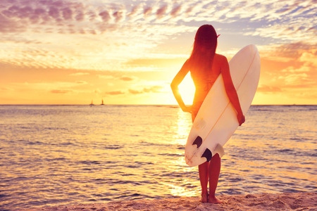 Surfer girl surfing looking at ocean beach sunset. Beautiful female bikini woman looking at water with standing with surfboard having fun living healthy active lifestyle. Water sports with model.