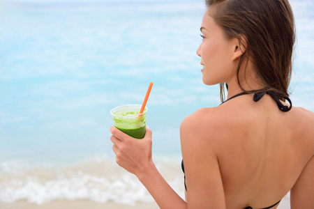 young girl bikini: Green vegetable smoothie - woman drinking detox vegetables smoothie in bikini after swimming in ocean sea on beach. Fitness healthy lifestyle concept with beautiful multiracial Asian Caucasian model