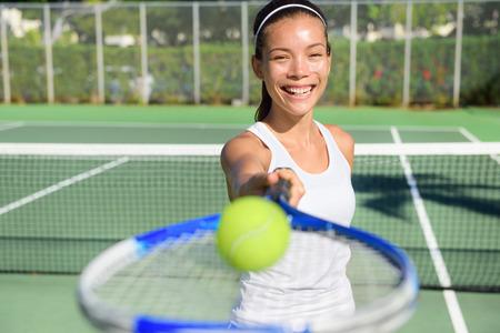 invitando: Retrato del jugador de tenis. Mujer que muestra la pelota de tenis y raqueta sonriendo feliz. Atleta de sexo femenino que te invita a jugar al tenis. Deporte activo saludable y estilo de vida saludable concepto al aire libre.