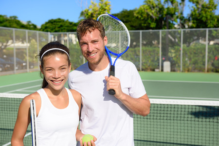 Tennis players portrait on tennis court outdoor. Couple or mixed double tennis partners after playing tennis outside in summer. Happy young people, woman and man living healthy active sport lifestyle.