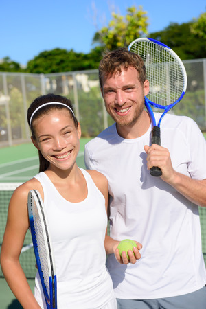 active lifestyle: Tennis sport - Mixed doubles couple players portrait relaxing after playing game outside in summer. Happy smiling people on outdoor tennis court living healthy active lifestyle. Woman and man athletes Stock Photo