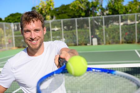 invitando: El jugador de tenis de hombre joven muestra la bola y la raqueta. Sonriendo feliz atleta masculino que te invita a jugar al tenis. Deporte activo saludable y estilo de vida saludable concepto. Foto de archivo