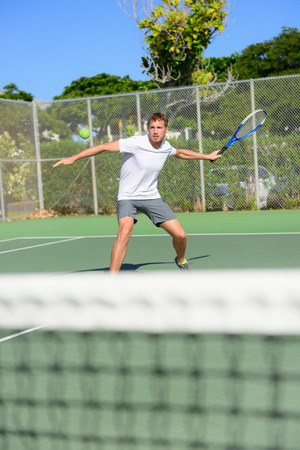 forehand: Tennis player - man hitting forehand playing outside on hard court. Male sport fitness athlete practicing in summer outdoors living healthy active lifestyle.