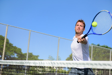 Tennisser man te raken bal in een volley. Mannelijke sport fitness atleet tennissen op buiten hard court in de zomer. Gezonde actieve leefstijl concept. Stockfoto