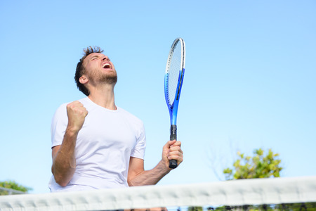 Tennis player man winning cheering celebrating victory. Winner man happy in celebration of success and win. Fit male athlete on tennis court outdoors holding tennis racket in triumph by the net.
