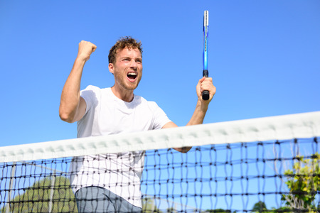 tennis net: Tennis player celebrating victory. Winning cheering man happy in celebration of success and win. Fit male athlete winner on tennis court outdoors holding tennis racket in triumph by the net.