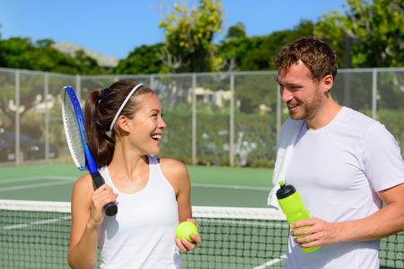 jugando tenis: Deporte Tenis - Pareja relajante después de jugar partido de tenis al aire libre en verano. Amigos felices sonrientes en la pista de tenis al aire libre viven saludable estilo de vida saludable activa. Mujer y hombre atletas. Foto de archivo