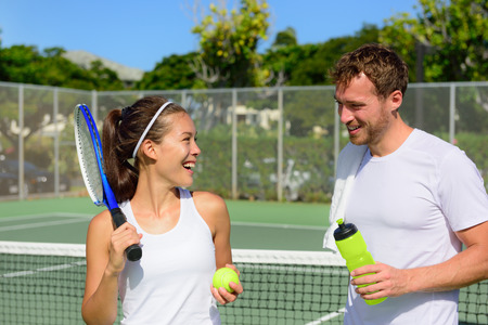 Tennis sport - couple relaxing after playing game of tennis outside in summer. Happy smiling friends on outdoor tennis court living healthy active fitness lifestyle. Woman and man athletes. Stock Photo