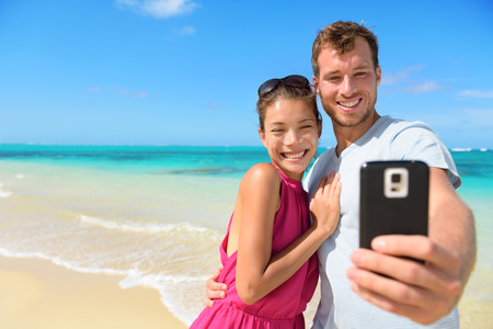 Beach vacation couple taking selfie photograph using smartphone relaxing and having fun holding smart phone camera. Young beautiful multicultural Asian Caucasian couple on summer beach. photo