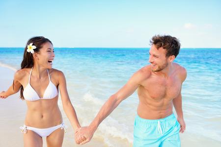 Quelques plage en se amusant sur la plage heureux vacances pendant les vacances d'été. Multiraciale quelques ajustement courir ensemble main dans la main en riant au soleil. Les jeunes adultes de forme bonheur insouciant. Banque d'images - 37760552