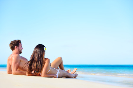 Beach vacation couple relaxing tanning in summer. Beautiful young adults on holidays lying down on white sand enjoying travel getaway under blue sky by turquoise water ocean sea. Multiracial couple. photo