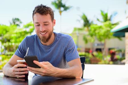 summer: Smartphone mensajes de texto sms hombre que bebe la bebida de café frío en la cafetería al aire libre en la terraza en verano. Feliz lectura informal urbano joven adulto celebración de teléfono o utilizando aplicaciones para conectar con amigos en las redes sociales.
