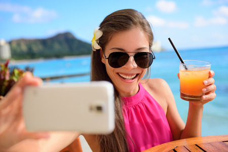 season photos: Selfie woman taking self portrait at beach bar during holidays. Young Asian adult holding smartphone camera to take a picture of herself during her summer vacations in Waikiki, Honolulu, Hawaii, USA.