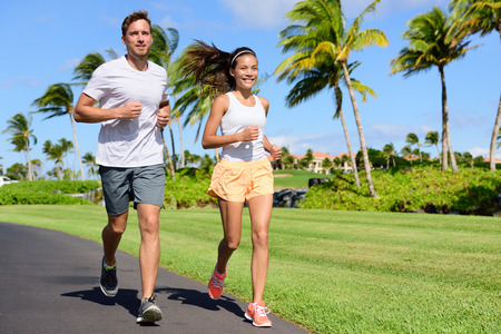 asian man: Sport couple exercising running outside on street in summer. Happy active young fit adults jogging together with tropical background in city park or resort road. Asian and Caucasian people.