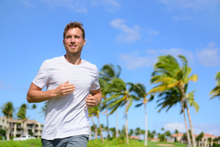 Healthy active man runner running in tropical park. Portrait of handsome young male jogger training cardio going for a run in city park or resort with palm trees in the background in summer.