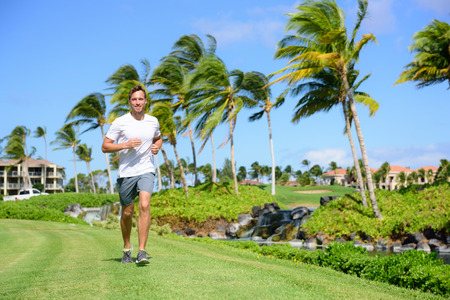 Outdoor exercise man running on grass in city park, resort area or upscale community. Happy young male runner staying fit exercising and living a healthy lifestyle training outside in summer nature. Stock Photo