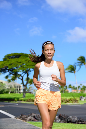 staying in shape: Young woman jogging on city street during summer. Asian girl doing cardio exercise training the body to lose weight and staying fit and in shape. Portrait waist up of female jogger going for a run. Stock Photo