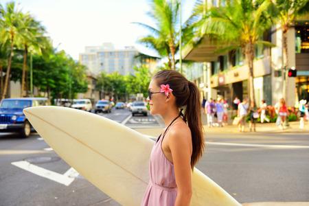 hawaiana: Surfer mujer caminando en la ciudad con tabla de surf para ir a surfear. Urban concepto de surf hawaiano. Muchacha asi�tica que sostiene calle cruce tabla de surf para ir a la playa. Ciudad de Waikiki, Honolulu, Oahu, Hawaii, EE.UU..