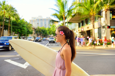 Surfer woman walking in city with surfboard to go surfing. Urban Hawaiian surf concept. Asian girl holding surf board crossing street to go to the beach. Waikiki, Honolulu city, Oahu, Hawaii, USA. Stock Photo