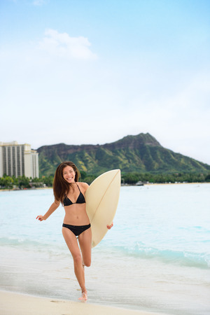 diamond head: Happy surfer girl surfing on Waikiki Hawaiian Beach, Hawaii. Asian woman running to the waves with surfboard in Honolulu city, famous Diamond Head in the background during the summer travel holidays.