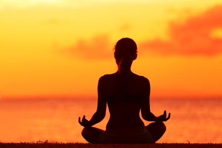 Zen yoga vrouw doet meditatie op het strand - wellness-concept. Vrouwelijke silhouet ontspannen zitten bij zonsondergang achtergrond mediteren bij oceaan retraite. Zomer oranje zonsopgang hemel.