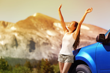 holiday trip: Happy free woman next to car relaxing on summer road trip adventure travel with open arms up showing freedom. Nature travel concept with mountain background in the USA. Young Asian adult driver.